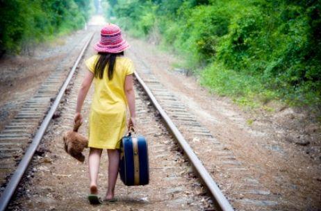 Foto de menina indo embora por um trilho de trem.