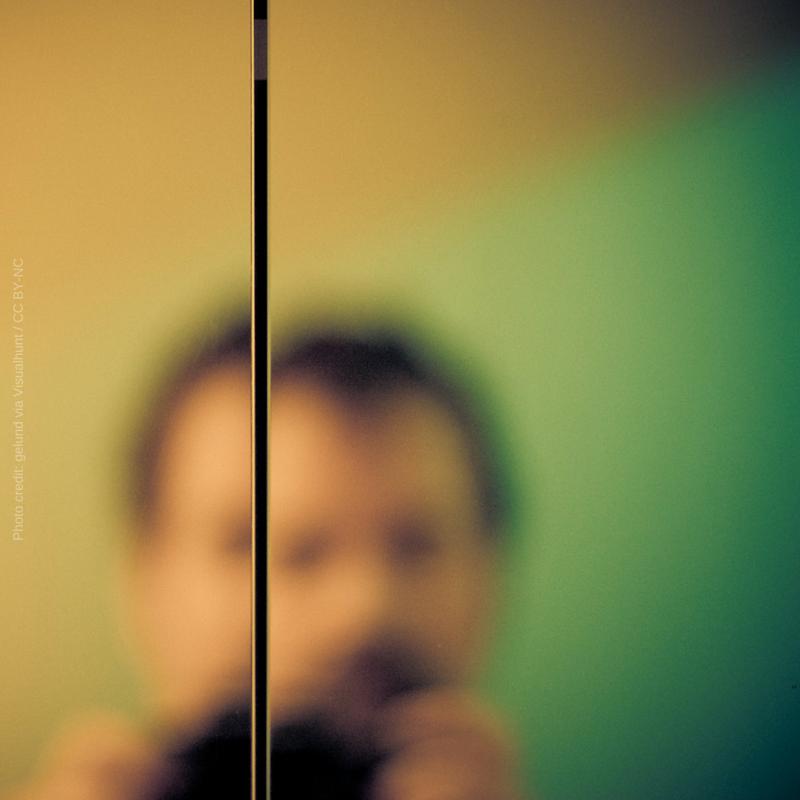 homem se vê desfocado no espelho