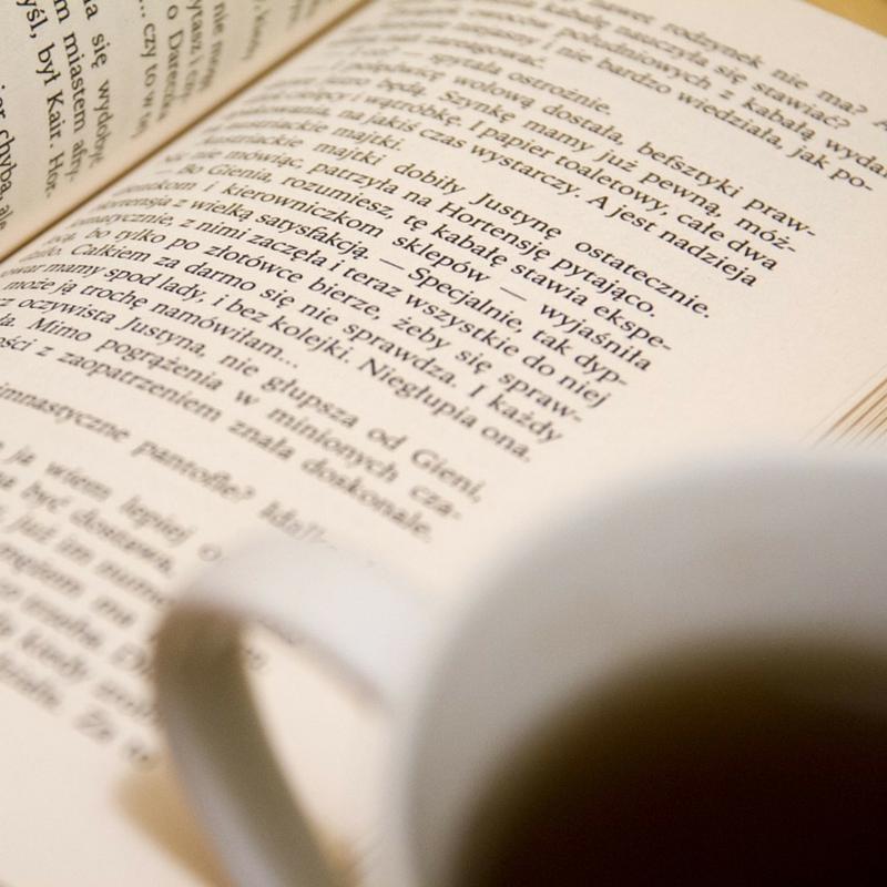 Um livro aberto e uma xícara de café
